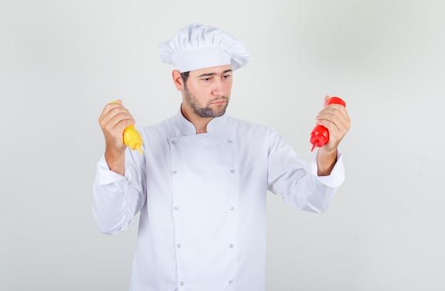 Chef hombre sosteniendo botellas de salsa de tomate y mostaza en uniforme blanco