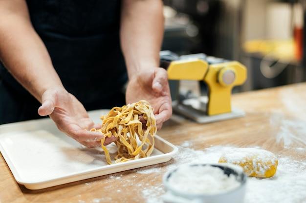 Chef hombre sosteniendo pasta fresca
