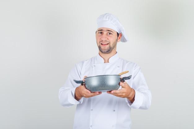 Chef hombre sosteniendo sopa en una cacerola en uniforme blanco y mirando feliz