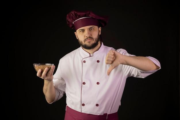 Chef insatisfecho hombre en uniforme sostiene tazón con trigo sarraceno muestra signo de disgusto