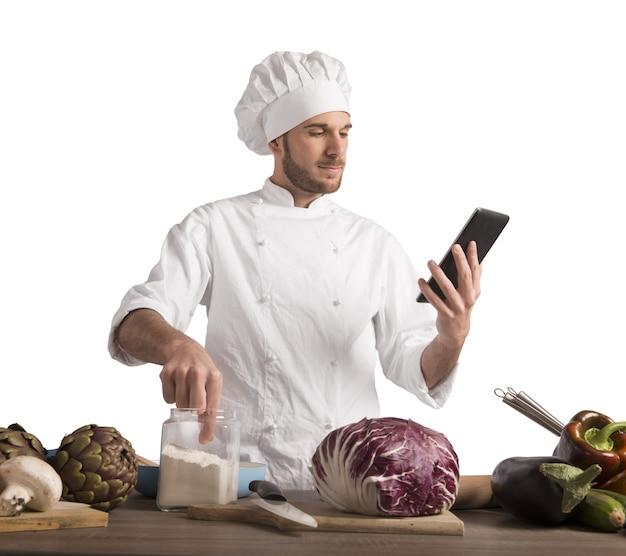 El chef lee una receta de la tableta.
