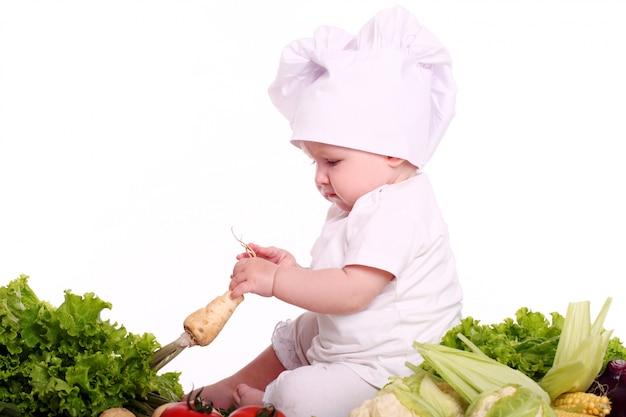 Chef lindo bebé con diferentes verduras