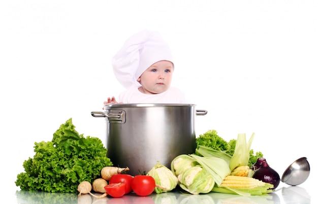 Chef lindo bebé con olla grande y verduras