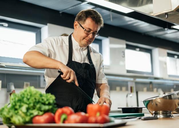 Chef macho picar tomates en la cocina