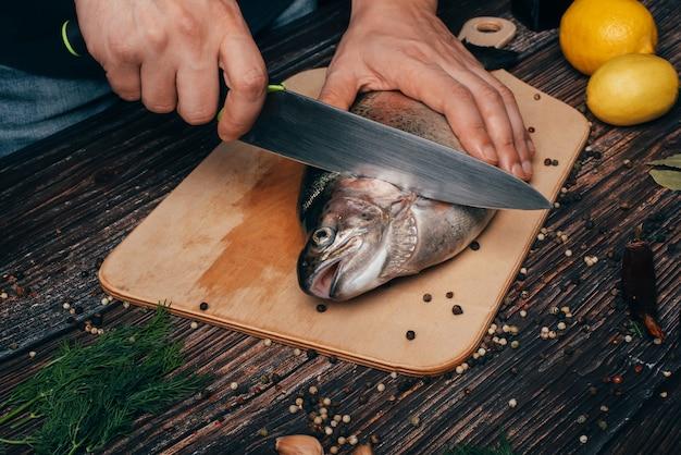 Chef manos con un cuchillo cortando pescado en una mesa de madera en la cocina