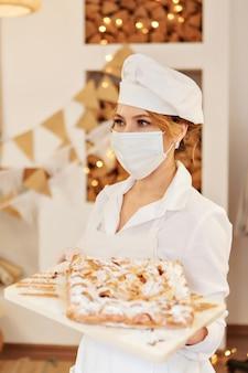 Un chef con una máscara médica sostiene un pastel sobre una tabla de cortar. la comida está lista para comer. masa de hojaldre