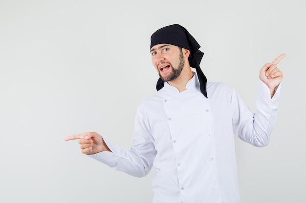 Chef masculino apuntando con el dedo hacia arriba y hacia abajo en uniforme blanco y mirando indeciso, vista frontal.