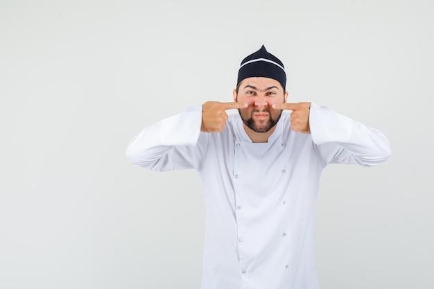 Chef masculino apuntando a su nariz con uniforme blanco y mirando extraño, vista frontal.