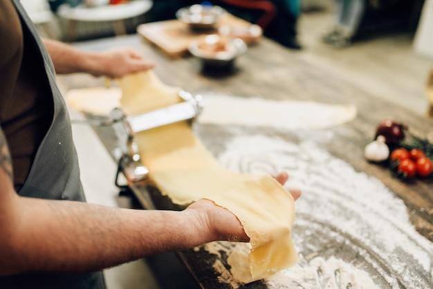 Chef masculino cocinando fettuccine en máquina de pasta