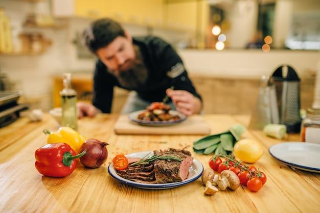 Chef masculino decora con hierbas un plato de carne para gourmets