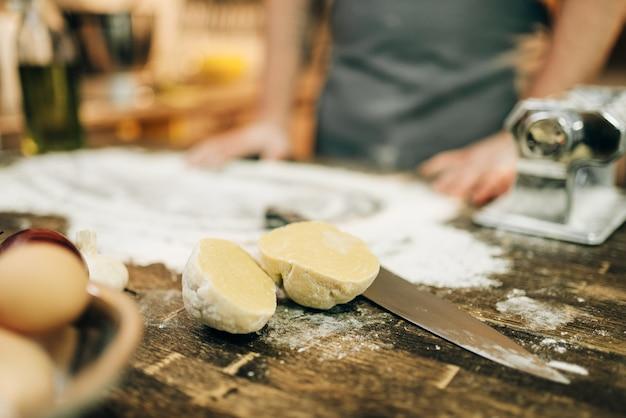 Chef masculino en delantal, harina, masa, huevos y máquina de pasta en mesa de madera. ingredientes para cocinar espaguetis caseros