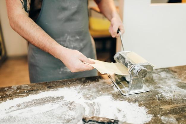 Chef masculino en delantal trabaja con máquina de pasta
