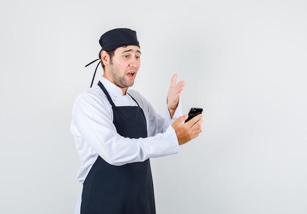 Chef masculino enojarse en videollamada en uniforme, delantal, vista frontal.