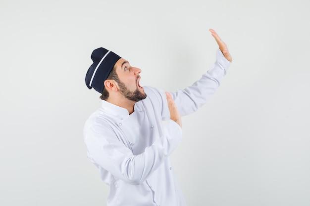 Chef masculino levantando la mano para defenderse en uniforme blanco y mirando asustado. vista frontal.