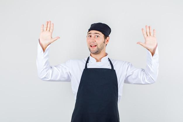 Chef masculino levantando las manos en señal de rendición en uniforme, delantal, vista frontal.