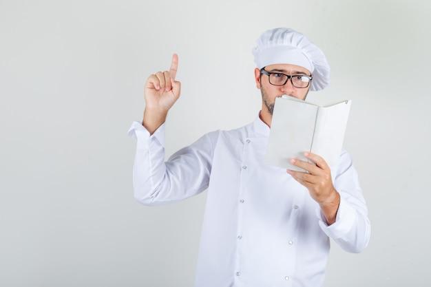 Chef masculino leyendo el libro y haciendo el dedo hacia arriba en uniforme blanco