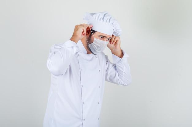 Chef masculino con máscara médica en uniforme blanco y mirando con cuidado