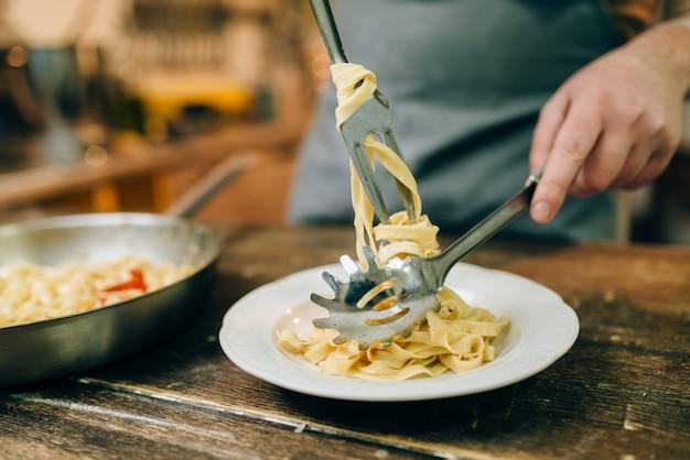 Chef masculino pone pasta fresca en un plato, sartén en la mesa de la cocina de madera. proceso de preparación de fettuccine casero. cocina tradicional italiana