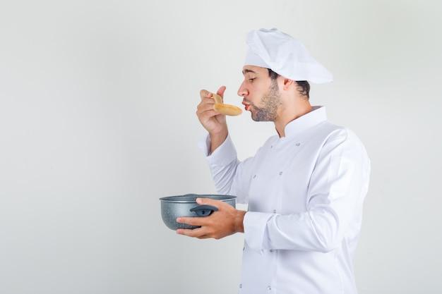 Chef masculino en uniforme blanco soplando sobre sopa caliente y sosteniendo una cacerola