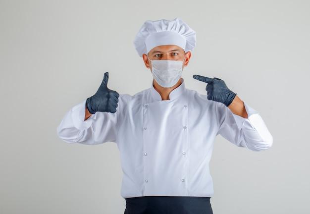 Chef masculino en uniforme, delantal y sombrero mostrando máscara y pulgares arriba y mirando con cuidado