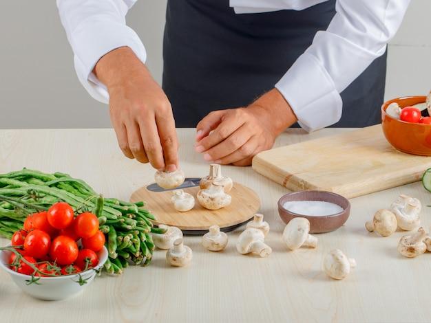 Chef masculino en uniforme y delantal tomando hongos para picar en la cocina