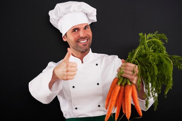 Chef con montón de zanahorias mostrando los pulgares para arriba