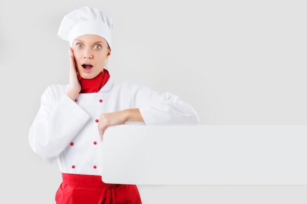 Chef mostrando signos en blanco. mujer chef, panadero o cocinero sorpresa con cartel de papel blanco en blanco