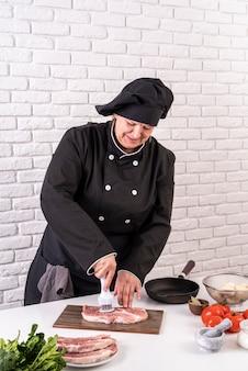 Chef mujer ablandando la carne en la cocina