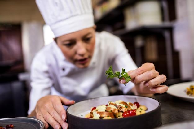 Chef mujer adornando deliciosos postres en un plato