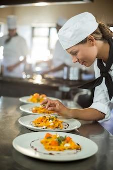 Chef mujer adornar plato de comida