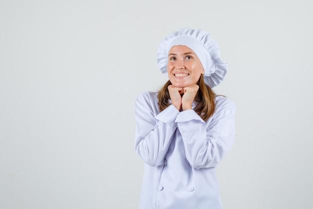 Chef mujer apoyando la barbilla en los puños en uniforme blanco y mirando esperanzado