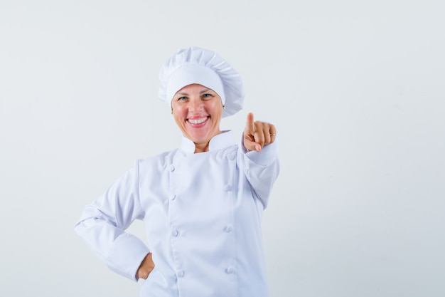 Chef mujer apuntando hacia adelante con uniforme blanco y mirando alegre