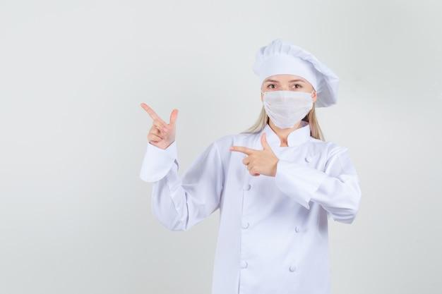 Chef mujer apuntando al lado con gesto de pistola en uniforme blanco