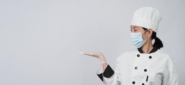 Chef mujer asiática en uniforme de color blanco con higiene como mascarilla médica y guante de goma para prevenir o proteger la pandemia de covid-19 o coronavirus.