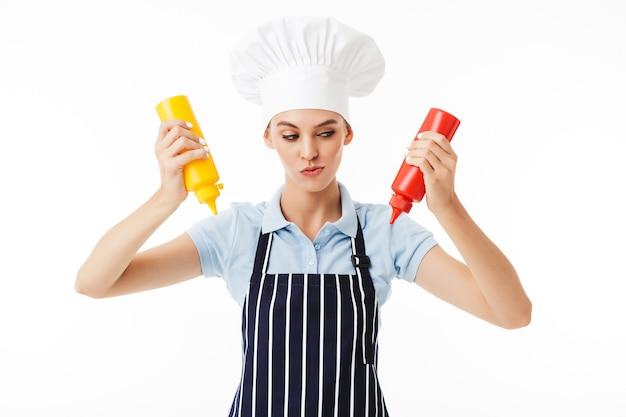 Chef mujer astuta en delantal a rayas y sombrero blanco pensativamente