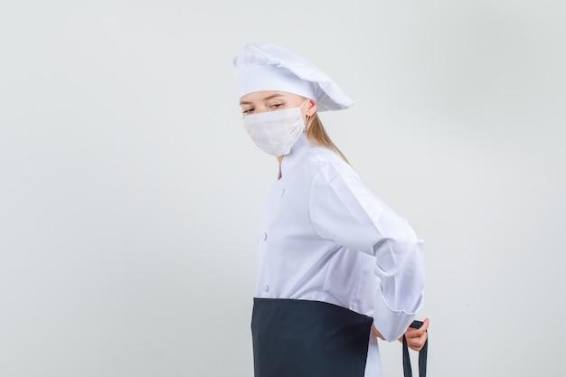 Chef mujer atar delantal alrededor de la cintura en uniforme blanco, máscara médica.