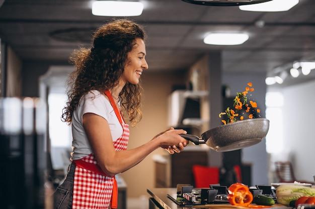 Chef mujer cocinar verduras en sartén
