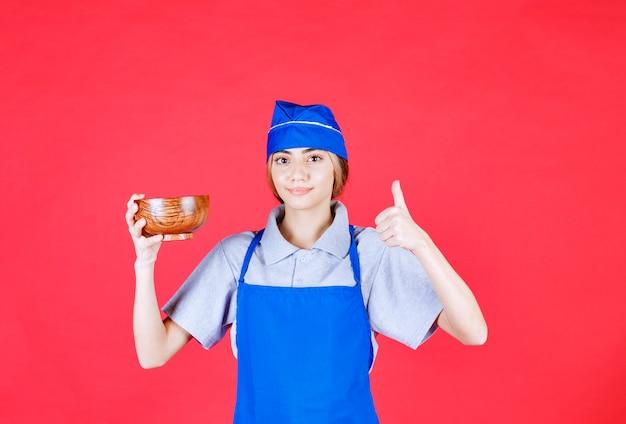 Chef mujer en delantal azul sosteniendo una taza de fideos de cobre chino y mostrando signo de mano de disfrute