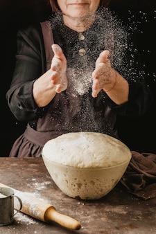 Chef mujer espolvoreando sus manos con harina antes de manipular la masa de pizza