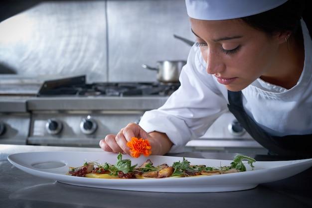 Chef mujer guarnición de flores en el plato en la cocina