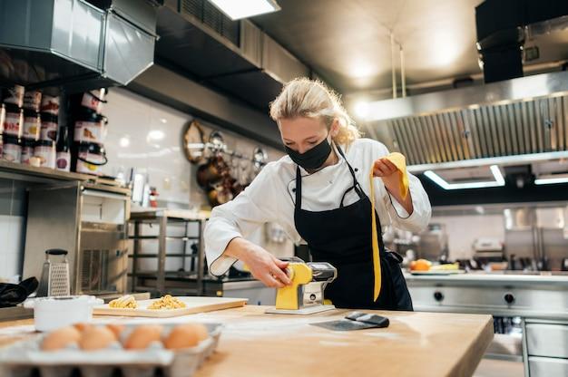 Chef mujer con máscara rodando masa de pasta