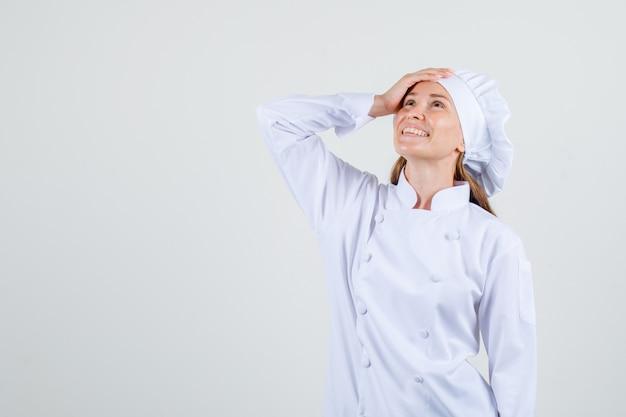 Chef mujer mirando hacia arriba con la mano en la cabeza en uniforme blanco y mirando contento. vista frontal.