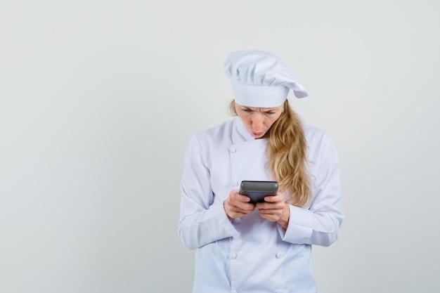 Chef mujer mirando calculadora en uniforme blanco y mirando desconcertado