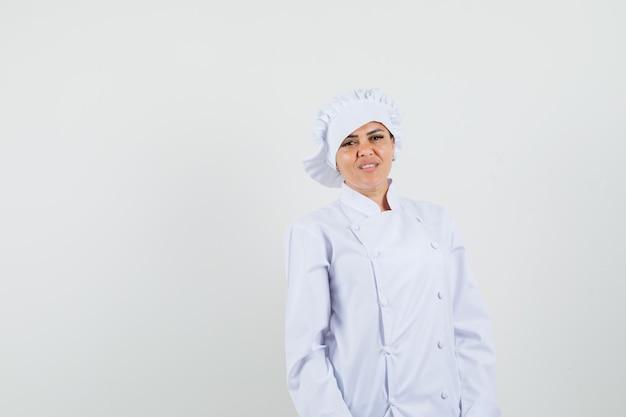 Chef mujer mirando a cámara en uniforme blanco y mirando alegre.