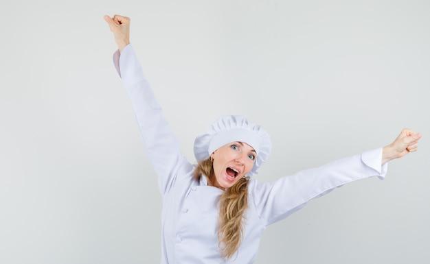 Chef mujer mostrando gesto ganador en uniforme blanco y mirando feliz