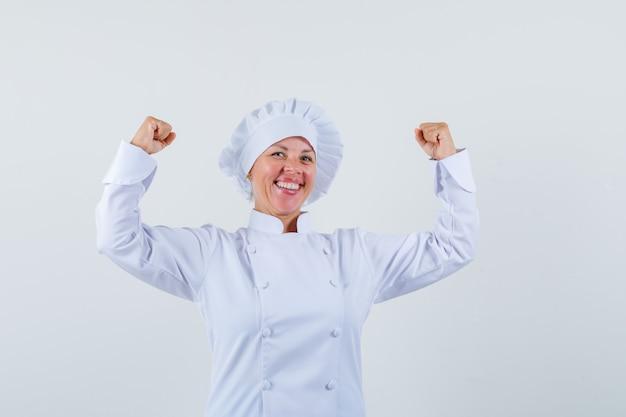 Chef mujer mostrando gesto ganador en uniforme blanco y mirando feliz.