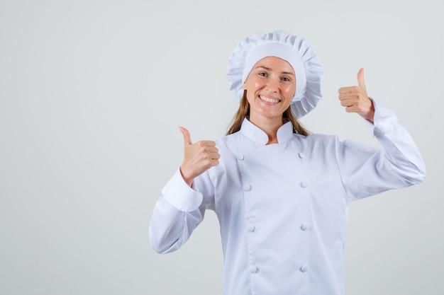 Chef mujer mostrando los pulgares para arriba en uniforme blanco y mirando feliz
