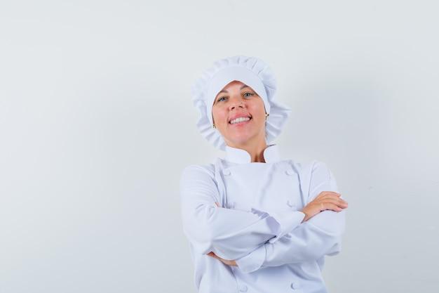 Chef mujer de pie con los brazos cruzados en uniforme blanco y mirando confiado