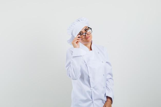 Chef mujer quitándose las gafas en uniforme blanco y mirando sensible