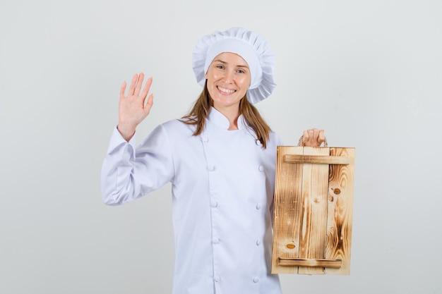 Chef mujer sosteniendo bandeja de madera con palma levantada en uniforme blanco y mirando alegre